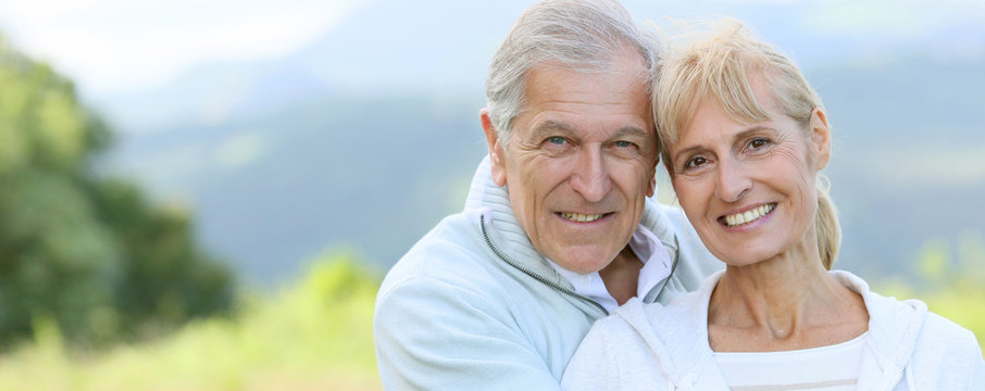 Portrait of cheerful senior couple embracing each other, template