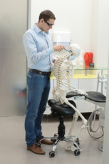 dentist as a patientexpert analysing  human skeleton model as a dentist  in sitting,leaning position at work - occupational disease concept