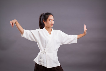 Photo sur Toile Combat woman fighter portrait; asian woman practicing chinese martial arts, gongfu, kungfu, taichi, taiji, MMA studio isolated portrait; girl fighter training concept; 20s young adult asian woman model