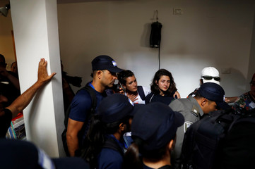 Women stand in a house as Israeli security forces evacuate Jewish settler families from the illegal outpost of Netiv Ha'avot in the occupied West Bank