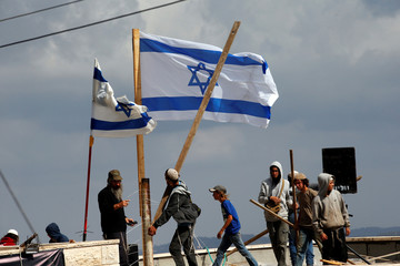 Protestors carry wooden sticks as they stand on a roof during the evacuation of Jewish settler families from the illegal outpost of Netiv Ha'avot in the occupied West Bank