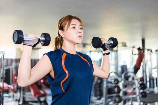 Young Asian woman working out and doing fitness training at a local gym