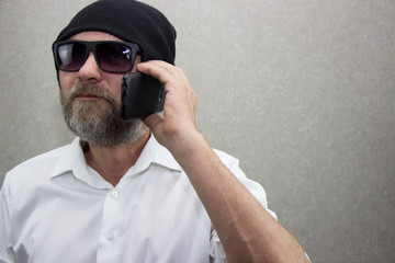 A man in a shirt with a beard wearing glasses and a hat talking on his cell phone
