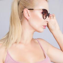 Close-up portrait of a blonde woman in black sunglasses
