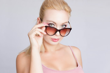 Close-up portrait of a blonde woman in black sunglasses