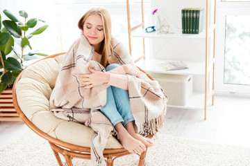 Portrait of calm cute girl with barefoot sitting on cane armchair covered by plaid keeping eyes closed getting warm enjoying domestic atmosphere having good memories