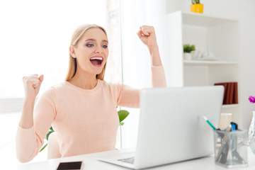 Portrait of cheerful positive girl celebrating successfully pass exams with raised fists looking at screen of computer having great results sitting indoor