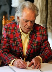 Bridegroom dressed in scottish tartansuit reads the contract during the wedding ceremony