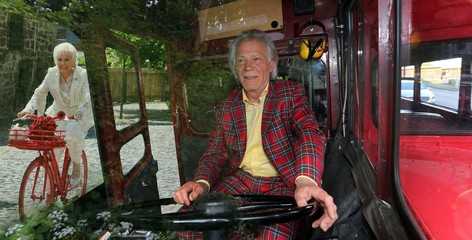 The happy bride, dressed in a romantic bridal suit, with a red retro bicycle with a red horn, rides next to the English red double-decker bus, driven by the bridegroom, dressed in steward tartan suit