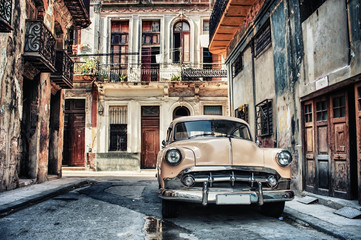 Old classic car in a street of havana with buildings in background
