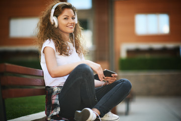 Young woman sitting on bench with legs crossed and listening to the music.