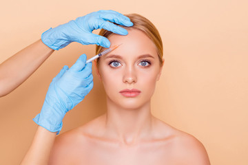 Portrait of attractive calm cute model making lifting botox collagen injection in forehead isolated on beige background, looking at camera. Perfection wellbeing wellness concept