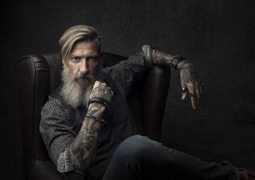 Porträt eines tätowierten bärtigen Mannes, der in einem Sessel sitzt