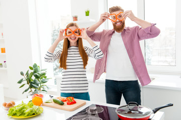 Ha-ha! Vegan veggie healthy nutrition fitness meal lifestyle laugh laughter concept. Portrait of comic cheerful couple making eyeglasses with red papper standing near table stove in modern kitchen