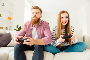 Champion addiction students wife husband car race emotion expressing concept. Excited cunning nervous cheerful joyful gamers using  controllers for playing video games sitting on beige divan