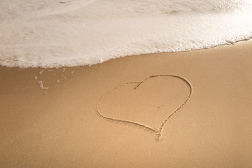 Heart drawn on a sand of beach with the wave of the sea Romantic love background valentine Day theme