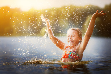 little girl playing in the river. A girl with blond hair raises her hands up in the water and splashes water drops Wall mural