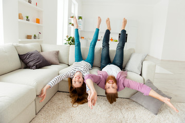 Coziness holiday house friendship funny partners lifestyle leisure concept. Excited cheerful joyful funky rejoicing lovers fooling around lying on divan in living room wearing casual outfit clothes