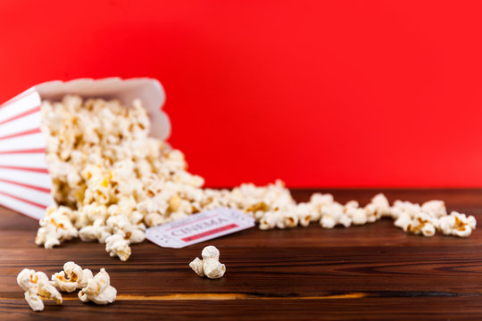 Red and White Bucket Of Popcorn With Two Red Movie Tickets