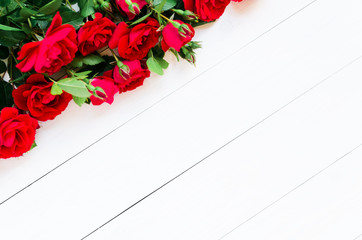 Home roses on a white wooden table flat lay. With copy space