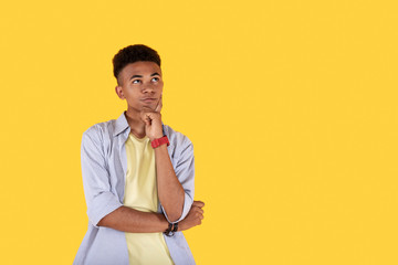 Creative ideas. Smart creative man standing against yellow background while developing new ideas