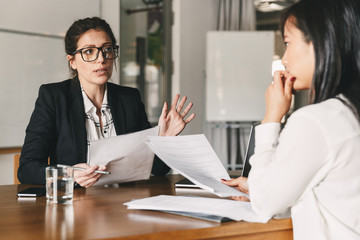 Photo of strict caucasian woman holding resume, and negotiating with female candidate during corporate meeting or job interview - business, career and placement concept