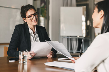 Portrait of smiling businesswoman holding resume and talking to female candidate, during corporate meeting or job interview - business, career and placement concept