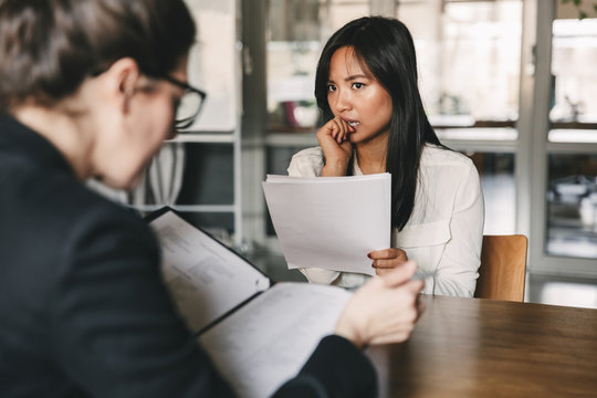Image of concentrated tense asian woman looking at businesswoman, while sitting at table in office during job interview - business, career and recruitment concept