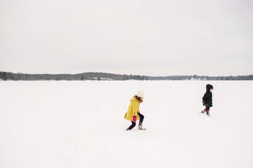 Boy and girl walking across a frozen lake