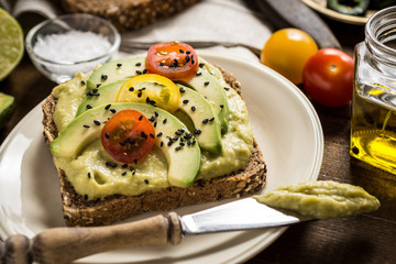Avocado Spread and Slices with Cherry Tomato and Black Sesame on Wooden Background as Vegetarian Food Concept