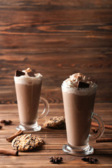 Glass cups of tasty cocoa drink with cream and sweets on wooden table