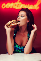 Sexy woman sitting at table in night club or bar and eating hamburger. Fashion style portrait