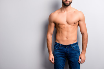 Cropped close up photo of handsome attractive ideal perfect stunning strong muscular flawless man's body with six-pack wearing dark blue denim jeans isolated on gray background copy-space