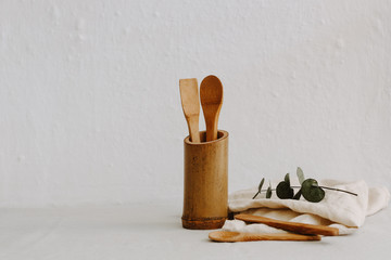 Set of wooden kitchen utensils, linen napkin and eucalyptus
