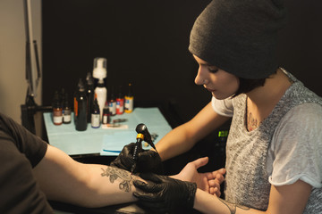 Young woman tattooist doing tattoo on male arm