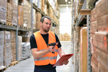 logistician in a warehouse of a forwarding agency scans packages for dispatch // Arbeiter in einer Spedition im Warenlager - Transport von Gütern im Onlinehandel