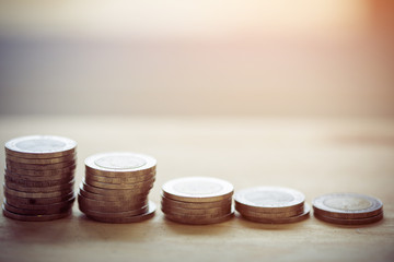 Coin stacks on a wood table background
