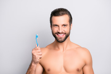 Close up portrait of excited satisfied handsome attractive with toothy beaming shiny smile with modern trendy hairstyle showing blue toothbrush isolated on gray background copy-space