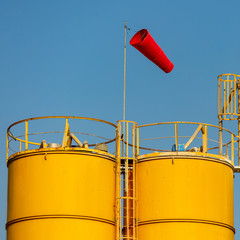 Red windsock on two yellow towers