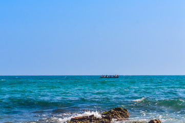 Photograph of Rowing Boat in Sea taken from a distance on a sunny day