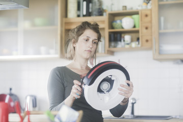 Woman standing in kitchen fixing a robotic vacuum cleaner