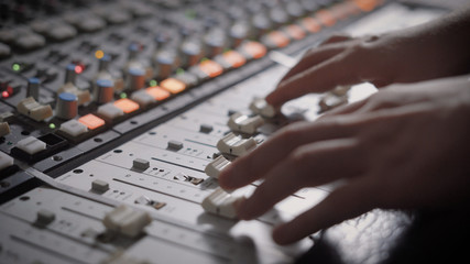 Close up shot of professional dj's hands working with a recording board in studio.