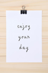 Enjoy your day quote on white paper