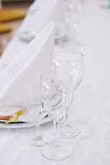 Table setting. Three empty glasses on white tablecloth.