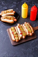 Photo on top of hotdogs on plate and board with ketchup and mustard