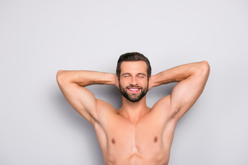 Attractive, stunning, manly, smiling macho isolated on gray background, having two arms behind the head and closed eyes, showing his shaven armpits - wellness, wellbeing concept Wall mural