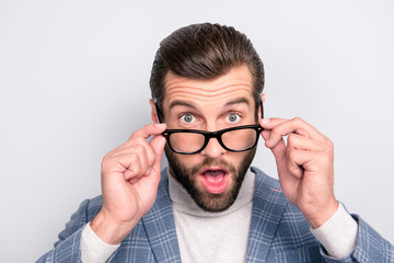 Clever, smart, harsh, attractive employee holding with fingers 2 eyelets of glasses on his face, looking out eyewear with astonished, shocked expression, wide open mouth and eyes over gray background
