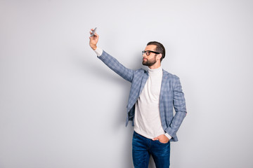 Virile, harsh, education, attractive man in jacket shooting self picture on smart phone front camera, holding hand in pocket of pants, standing over gray background