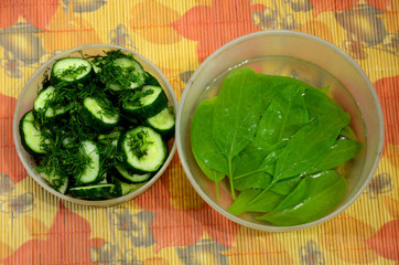 Two plastic bowls-one with sliced cucumber with dill, the second with spinach in the water.