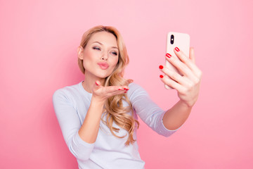 Portrait of lovely sweet girl having rest relax shooting self portrait on front camera of smart phone cellphone blowing air kiss isolated on pink background